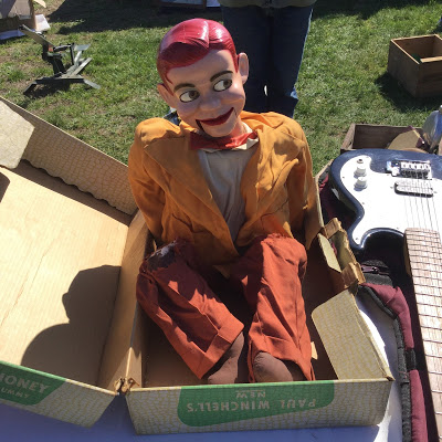 A ventriloquist dummy of Paul Winchell's Jerry Mahoney in its oriignal box sits on a flea market table next to an electric guitar, with green grass in the background.